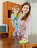 Mulher com o bebê que espana a tabela de madeira Imagens de Stock