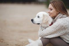 Mulher com o cão na costa de mar fotografia de stock