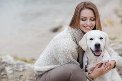 Mulher com o cão na costa de mar imagens de stock