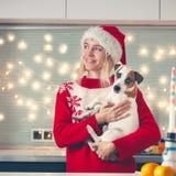 Mulher com o cão no chapéu do Natal fotografia de stock
