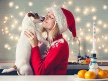 Mulher com o cão no chapéu do Natal fotos de stock royalty free