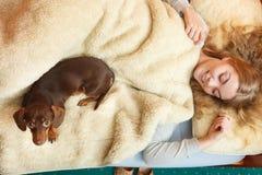 Mulher com o cão que acorda na cama após o sono Fotografia de Stock Royalty Free