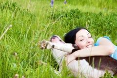 Mulher com o cão que joga na grama Foto de Stock