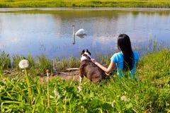 Mulher com o cão que senta-se no banco Fotografia de Stock