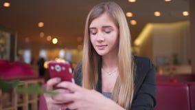 A mulher com o cabelo louro bonito no revestimento preto está sentando-se na loja do café Texting com ela filme