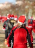 Mulher com o cabelo louro que corre durante a corrida de Santa Imagens de Stock Royalty Free