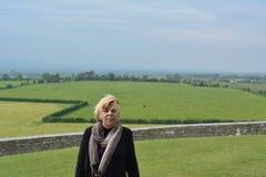 Mulher com o cabelo que torna-se em um vento contra campos verdes Foto de Stock Royalty Free