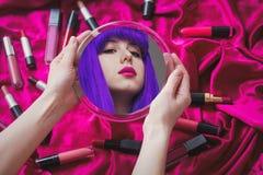 Mulher com o cabelo roxo que olha em um espelho com cosméticos imagem de stock