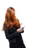 Mulher com o cabelo vermelho bonito que texting em um smartphone Imagem de Stock Royalty Free