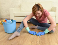 Mulher com o cabelo vermelho que limpa a casa que lava o assoalho em seus joelhos imagem de stock