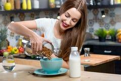 Mulher com o café da manhã do granola na cozinha imagem de stock royalty free
