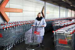 Mulher com o carrinho de compras no estacionamento Imagens de Stock