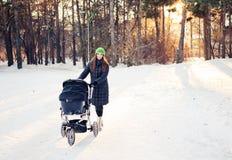 Mulher com o carrinho de criança que vai para uma caminhada dentro imagens de stock royalty free