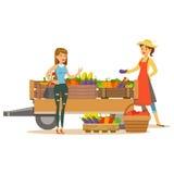 Mulher com o carro de madeira com vegetais e cliente, a exploração agrícola de Working At The do fazendeiro e a venda no produto  Imagens de Stock