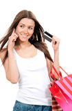 Mulher com o cartão de crédito dos sacos de compras à disposição que fala na pilha Fotos de Stock Royalty Free