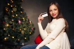 Mulher com o cartão de crédito na frente da árvore de Natal Fotografia de Stock