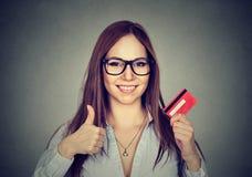 A mulher com o cartão de crédito que dá os polegares levanta o gesto de mão Imagem de Stock Royalty Free