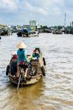 Mulher com o chapéu concal que conduz seu barco da máquina ao marke de flutuação Foto de Stock