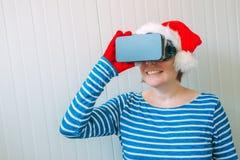 Mulher com o chapéu de Santa Claus do Natal e os auriculares de VR Fotografia de Stock