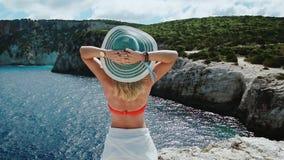 Mulher com o chapéu do sol em férias na apreciação de relaxamento de Grécia surpreendendo o litoral da paisagem na ilha de Kefalo vídeos de arquivo