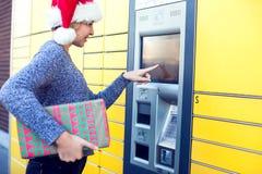 Mulher com o cliente do chapéu de Santa que usa o te automatizado do cargo do serviço do auto fotografia de stock