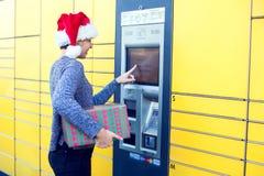Mulher com o cliente do chapéu de Santa que usa o te automatizado do cargo do serviço do auto foto de stock royalty free