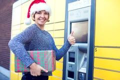 Mulher com o cliente do chapéu de Santa que usa o te automatizado do cargo do serviço do auto imagem de stock