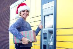 Mulher com o cliente do chapéu de Santa que usa o te automatizado do cargo do serviço do auto imagens de stock royalty free