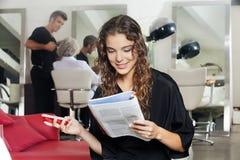 Mulher com o compartimento da leitura do telefone celular no cabelo foto de stock royalty free