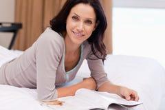 Mulher com o compartimento que encontra-se na cama fotografia de stock royalty free