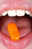 Mulher com o comprimido na lingüeta Imagens de Stock