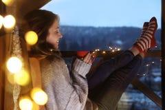 Mulher com o copo da bebida quente e das luzes de Natal que descansam no balcão fotografia de stock