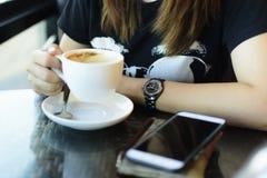 Mulher com o copo de café em sua mão com smartphone e etc. na tabela Foto de Stock