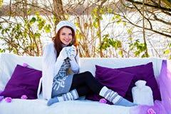 Mulher com o copo do chá que senta-se no sofá Fotografia de Stock Royalty Free