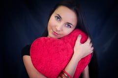 Mulher com o coxim dado forma coração Fotografia de Stock