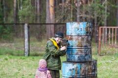 A mulher com o daugter da arma e do bebê que joga o lazer etiqueta Imagem de Stock Royalty Free