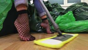 Mulher com o espanador que senta-se e que relaxa na sala suja video estoque