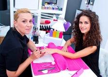 Mulher com o estilista no tratamento de mãos fotografia de stock royalty free
