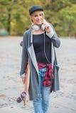 Mulher com o fones de ouvido que guarda o skate Fotos de Stock Royalty Free