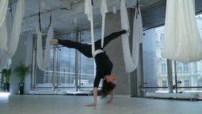 A mulher com o grande corpo que pendura com sua cabeça para baixo na rede da ioga no fitness center moderno com o grande assoalho filme
