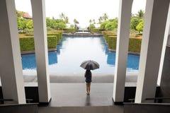 Mulher com o guarda-chuva que está pela piscina que olha a chuva Imagem de Stock Royalty Free