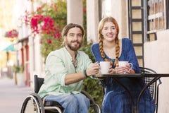 Mulher com o homem na cadeira de rodas que guarda copos de café Imagem de Stock Royalty Free