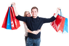 Mulher com o homem que sustenta o grupo dos sacos de compras fotografia de stock