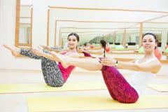 Mulher com o instrutor pessoal do instrutor que faz o exercício da aptidão dos músculos abdominais foto de stock