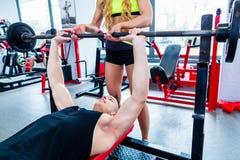Mulher com o instrutor pessoal na imprensa de banco no gym fotografia de stock