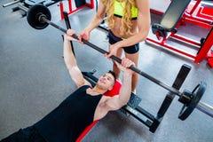Mulher com o instrutor pessoal na imprensa de banco no gym fotos de stock