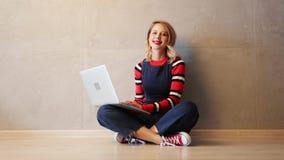 Mulher com o laptop que senta-se em um assoalho video estoque