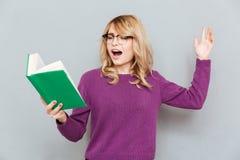 Mulher com o livro de leitura da expressão fotos de stock