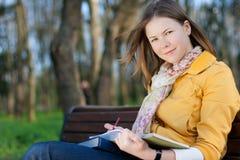 Mulher com o livro no parque Fotografia de Stock Royalty Free