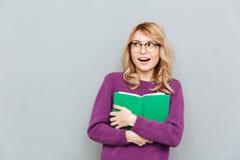 Mulher com o livro que olha afastado fotos de stock